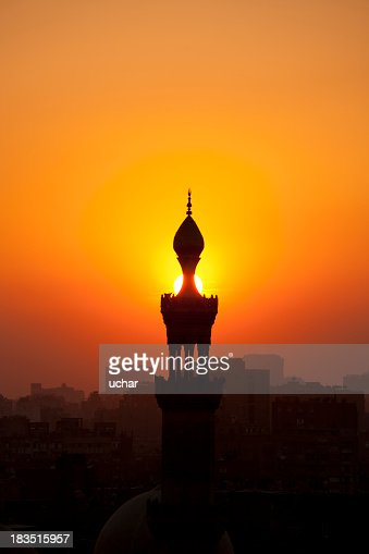 Orange sunset behind silhouette of mosque and town