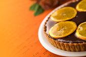Orange tart on plate, colored background