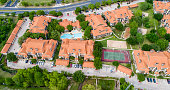 Aerial drone view Orange townhomes high above entire apartment complex view - Austin , Texas , USA - with tennis court , swimming pool