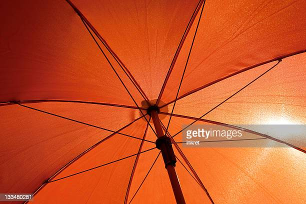 Orange umbrella from underneath with sun shining through