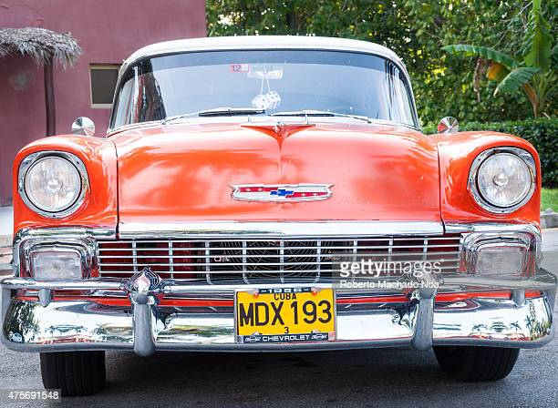 Orange vintage Chevrolet 57 redorange vintage Chevrolet car with chrome trim and Cuba license plate viewed from the front