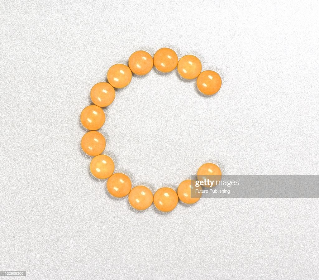 Orange vitamin C pills arranged in the shape of the letter C Studio shoot on September 14 United Kingdom