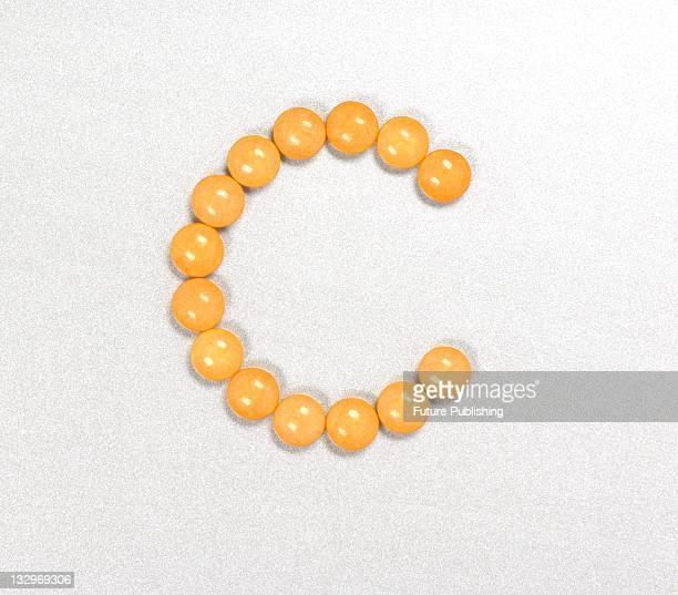 Orange vitamin C pills arranged in the shape of the letter C Studio shoot on September 14 United Kingdom