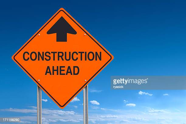 Orange Warning Construction Ahead Message Road Sign Over Blue Sky