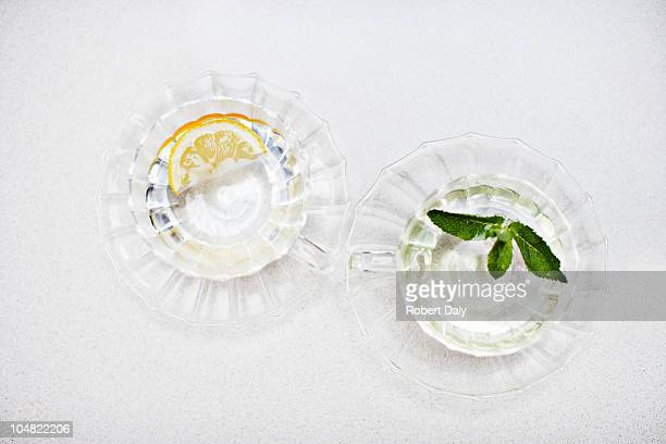 Orange wedge and mint sprig in glasses of water