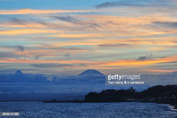 Orange-colored sunset clouds on Mt. Fuji and the beach in Kamakura city in Kanagawa prefecture in Japan