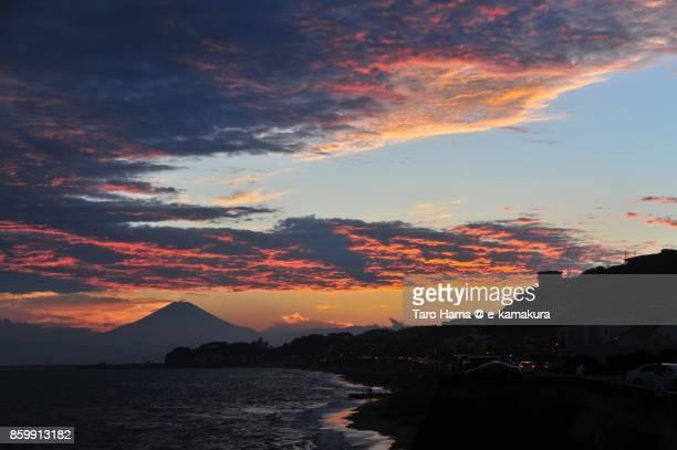 Orange-colored sunset clouds on Mt. Fuji, Enoshima Island and the beach in Kamakura city in Kanagawa prefecture in Japan