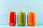 Orange/green/red colored smoothies / juice in a jar on a blue background.