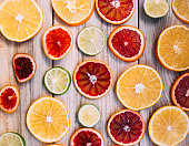 Juicy fresh plain and blood oranges and lime slices on the wooden table background,flat lay view