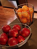 Oranges and pomegranates in kitchen baskets.
