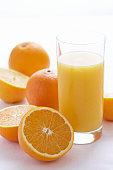 Oranges by orange juice in glass, close-up