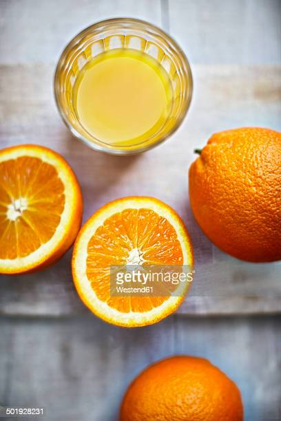Oranges, halves of oranges and a glass of orange juice on grey wood, elevated view
