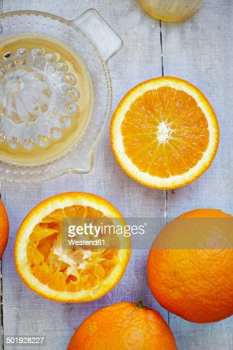 Oranges, halves of oranges and juice squeezer on grey wood, elevated view