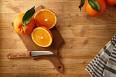 Kitchen table with oranges on a cutting board; one of which is cut in a half to prepare a healthy orange juice for breakfast.