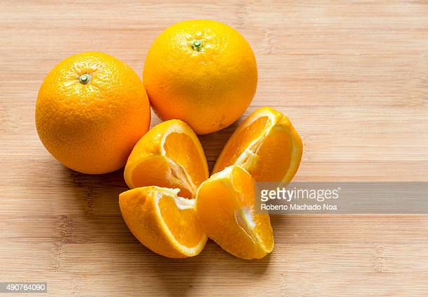 Oranges placed on a wooden chopping board There are two whole oranges and four quarter cut pieces