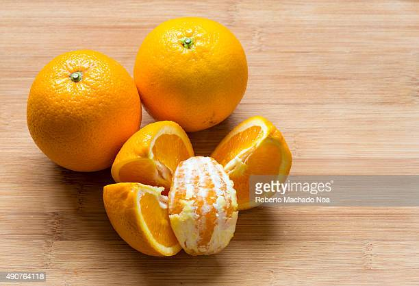 Oranges placed on a wooden chopping board There are two whole oranges and four quarter cut pieces with one peeled piece