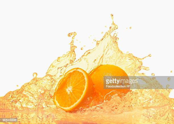 Oranges with splashing orange juice on white background, close up