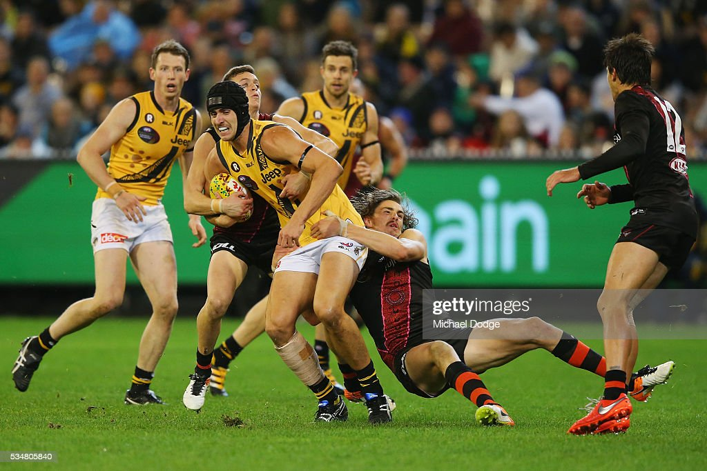 Orazio Fantasia of the Bombers and Joe Daniher (R) tackle Ben Griffiths of the Tigers during the round 10 AFL match between the Essendon Bombers and the Richmond Tigers at Melbourne Cricket Ground on May 28, 2016 in Melbourne, Australia.