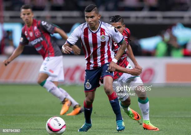 Orbelin Pineda of Chivas fights for the ball with Luis Perez of Necaxa during the third round match between Chivas and Necaxa as part of the Torneo...
