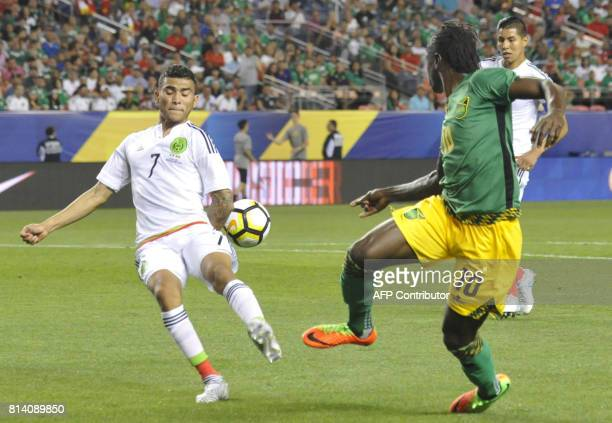 Orbelin Pineda of Mexico and Darren Mattocks of Jamaica vie for control of the ball during the Mexico vs Jamaica CONCACAF Group C Gold Cup soccer...