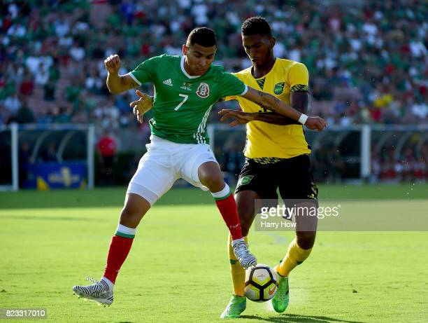 Orbelin Pineda of Mexico attempts to gain control of the ball from Damion Lowe of Jamaica during the first half of the CONCACAF 2017 semifinal at...