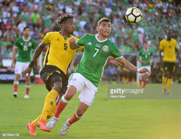 Orbelin Pineda of Mexico attempts to gain control of the ball in front of Alvas Powell of Jamaica during the first half of the CONCACAF 2017...