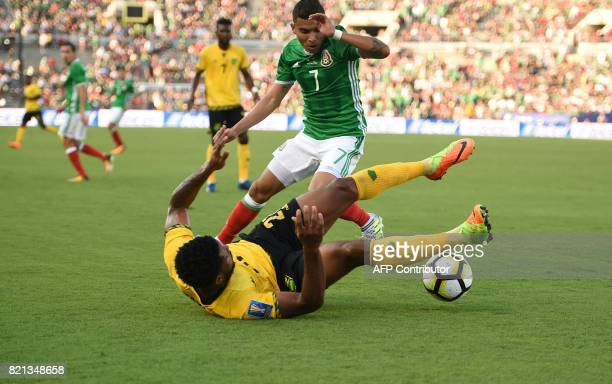 Orbelin Pineda of Mexico battles for a loose ball with Jermaine Taylor of Jamaica during their CONCACAF Gold Cup semifinal match on July 23 2017 at...