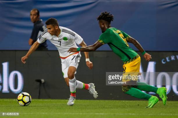 Orbelin Pineda of Mexico competes for ball with Oniel Fisher of Jamaica during a Group C match between Mexico and Jamaica as part of CONCACAF Gold...