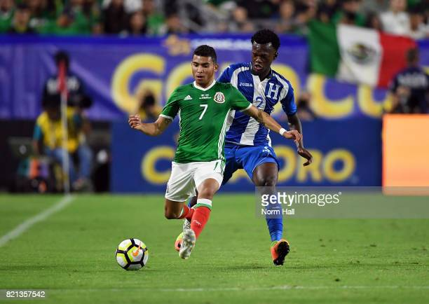 Orbelin Pineda of Mexico controls the ball against Felix Crisanto of Honduras in a quarterfinal match during the CONCACAF Gold Cup at University of...