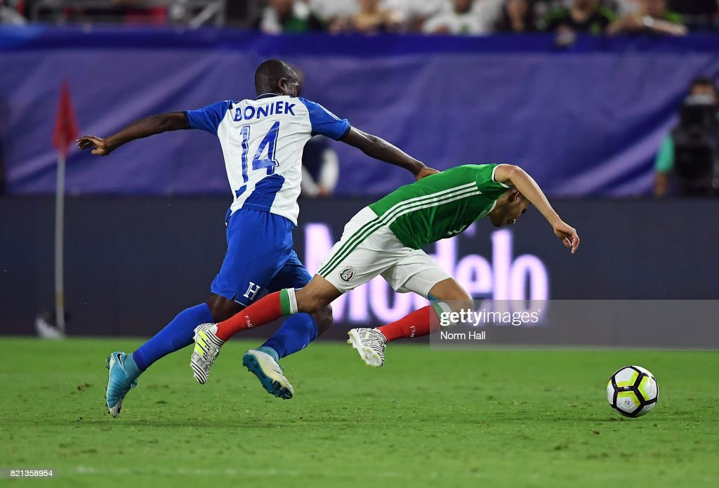Orbelin Pineda #7 of Mexico is pushed down from behind by Oscar Boniek Garcia #14 of Honduras in a quarterfinal match during the CONCACAF Gold Cup at University of Phoenix Stadium on July 20, 2017 in Glendale, Arizona.