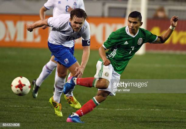 Orbelin Pineda of Mexico passes the ball ahead of David Thor Vidarsson of Iceland during their exhibition match at Sam Boyd Stadium on February 8...