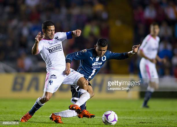 Orbelin Pineda of Queretaro fights for the ball with Walter Gargano of Monterrey during the 15th round match between Queretaro and Monterrey as part...