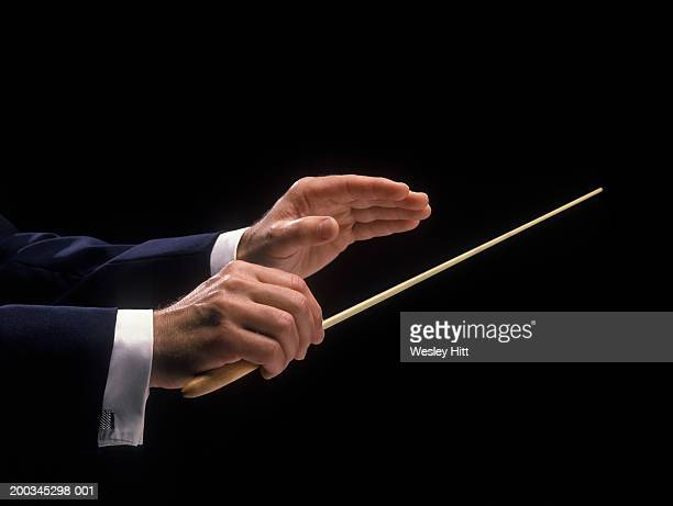 Orchestra conductor holding baton, side view, close-up of hands