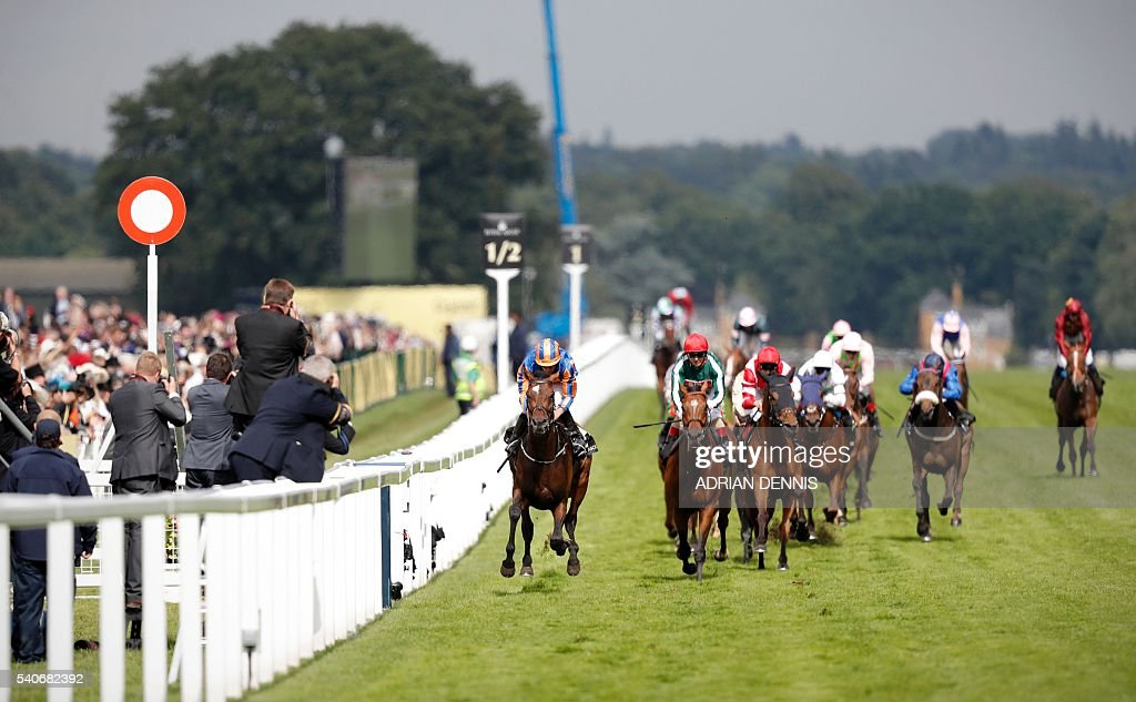 Order of St George (C) ridden by jockey Ryan Moore rides toward the finish line to win the Gold Cup in Honour of The Queen's 90th Birthday during Ladies day at Royal Ascot in Ascot, west of London, on June 16, 2016. The five-day meeting is one of the highlights of the horse racing calendar. Horse racing has been held at the famous Berkshire course since 1711 and tradition is a hallmark of the meeting. Top hats and tails remain compulsory in parts of the course while a daily procession of horse-drawn carriages brings the Queen to the course. / AFP / ADRIAN