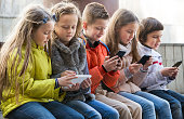 Ordinary kids sitting with mobile devices in street