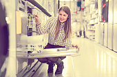 Ordinary woman choosing dishwashing machine in household appliances shop