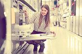 Ordinary woman choosing dishwashing machine in household appliances shop