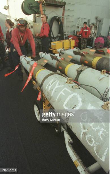Ordnance crewman aboard USS Enterprise moving missiles one inscribed NYFD WE OWE YOU in honor of NYC Fire Dept personnel killed in terror attacks of...