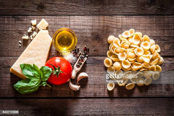 Orecchiette pasta with ingredients on rustic wooden table