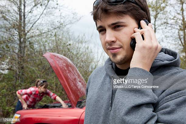 USA, Oregon, Ashland, Young man talking on mobile phone while man is attempting to fix broken car