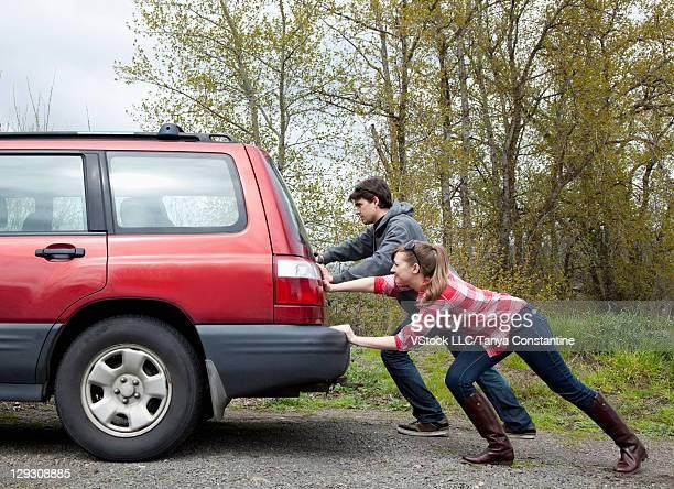 USA, Oregon, Ashland, Young woman and man pushing broken 4x4