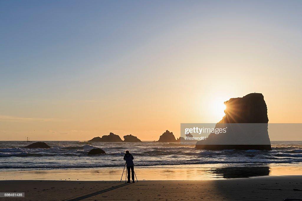 USA, Oregon, Bandon, Bandon Beach, Rocky needles at sunset, female fotographer at beach