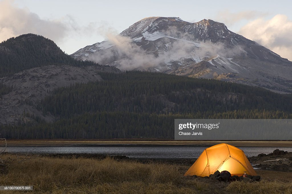 USA, Oregon, Bend, illuminated tent by lake in mountains : Stock Photo