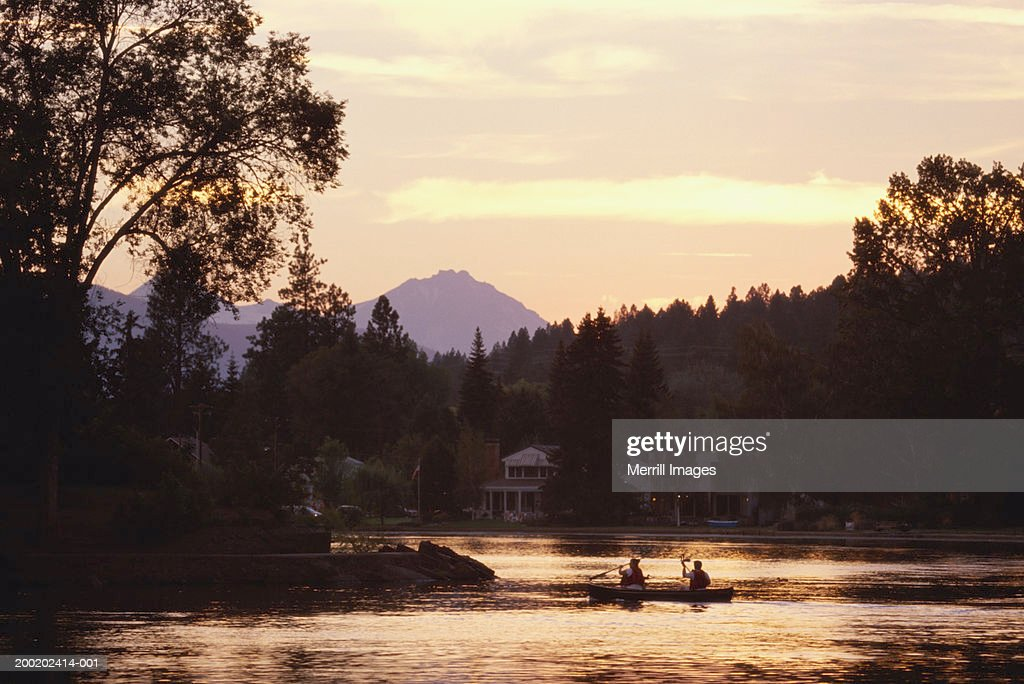 USA, Oregon, Bend, people in canoe on Mirror Pond, sunset : Stock Photo