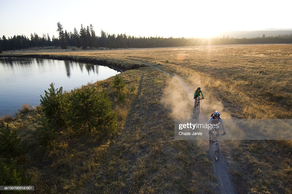 USA, Oregon, Bend, two cyclists on trail by river : Stock Photo