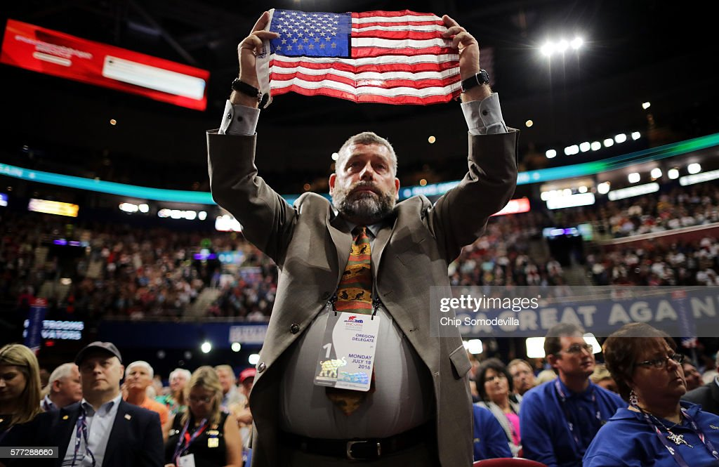 Oregon delegate Joseph Rice stands holding an American flag during a speech on the first day of the Republican National Convention on July 18 2016 at...