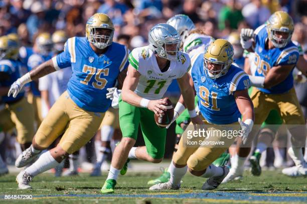 Oregon Ducks quarterback Braxton Burmeister scrambles out of the pocket to get away from UCLA Bruins defensive lineman Boss Tagaloa and UCLA Bruins...