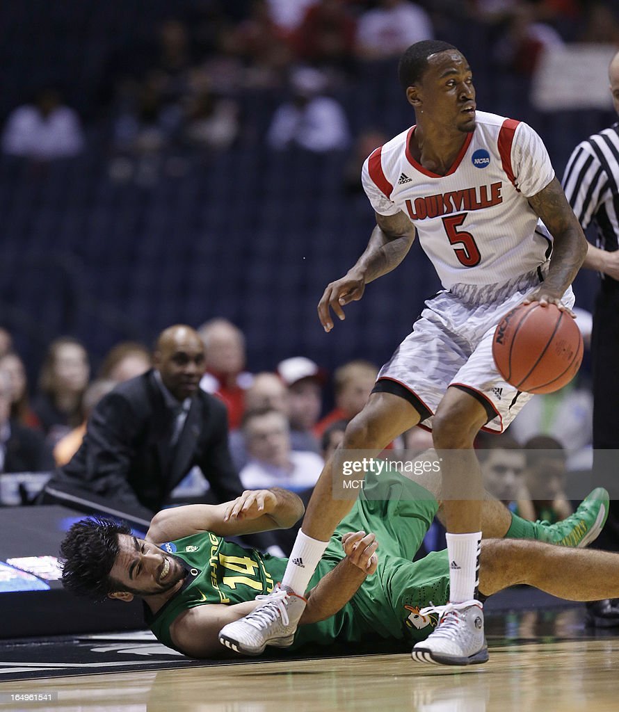 Oregon forward Arsalan Kazemi slides out of bounds trying to get the ball from Louisville guard Kevin Ware in first half action in their NCAA fourth...