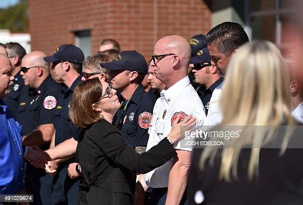 Oregon Governor Kate Brown thanks Fire Chief and first responder Greg Marlar at the conclusion of a press conference in Roseburg Oregon on October 2...