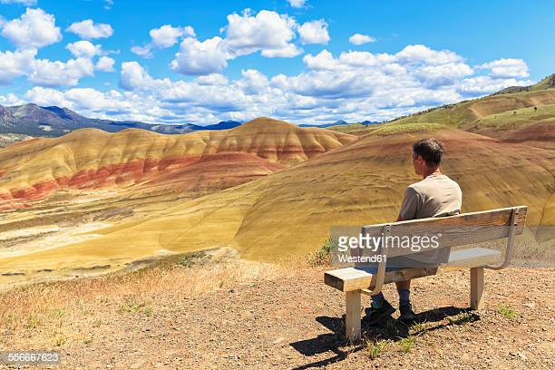 USA, Oregon, John Day Fossil Beds National Monument, tourist sitting on a bench looking at Painted Hills